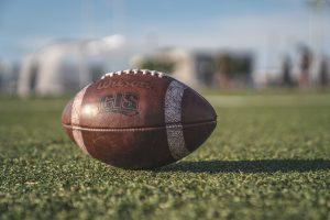 Ein Football liegt auf grünem Kunstrasen